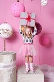 俏丽的女孩孩子在礼服的3岁 婴孩在他们的手上的拿着礼物 蔷薇石英室装饰了假日 免版税图库摄影