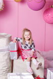 俏丽的女孩孩子在礼服的3岁 婴孩在他们的手上的拿着礼物 蔷薇石英室装饰了假日 库存图片