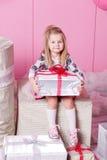俏丽的女孩孩子在礼服的3岁 婴孩在他们的手上的拿着礼物 蔷薇石英室装饰了假日 免版税库存照片