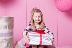 俏丽的女孩孩子在礼服的3岁 婴孩在他们的手上的拿着礼物 蔷薇石英室装饰了假日 库存照片