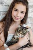 俏丽的女孩少年拿着猫的10-11年 图库摄影