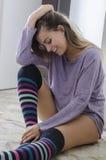 年轻俏丽的女孩微笑的坐佩带逗人喜爱的paja的地板 免版税库存照片