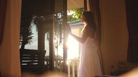 俏丽的女孩打开门在清早在与透镜火光作用的日出期间并且出去对大阳台 库存照片