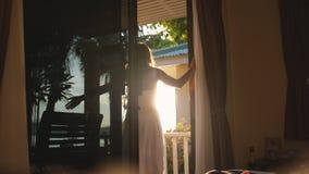 俏丽的女孩打开门在清早在与透镜火光作用的日出期间并且出去对大阳台 免版税库存图片