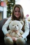 俏丽的女孩拥抱玩具熊 背景圣诞节关闭红色时间 免版税库存图片