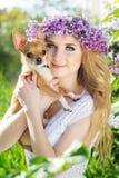 俏丽的女孩拿着她的小狗 免版税库存照片