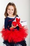 俏丽的女孩拿着有红色丝带的礼物盒 免版税库存图片