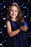 俏丽的女孩拿着蓝色圣诞树玩具 库存图片
