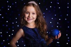 俏丽的女孩拿着蓝色圣诞节球 图库摄影