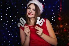 俏丽的女孩是纸数字2016年,圣诞节时间 库存图片