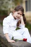 俏丽的女孩气味玫瑰室外在白色衣服 免版税库存照片