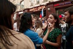 俏丽的女孩画俄罗斯的旗子一个另一个俏丽的女孩的面颊的 库存图片