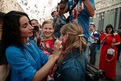 俏丽的女孩画俄罗斯的旗子一个另一个俏丽的女孩的面颊的 库存照片