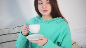 俏丽的女孩画象享用从杯子的一份咖啡在床上 股票视频