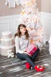 俏丽的女孩画象坐一个木地板 圣诞节家庭结构树 免版税图库摄影