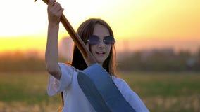 俏丽的女孩的关闭在太阳镜和弹投入吉他在室外在日落 情感更加滑稽的鬼脸仿效流行音乐 股票录像