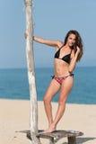 俏丽的女孩穿戴比基尼泳装,站立在沙子的一个木立场 库存照片