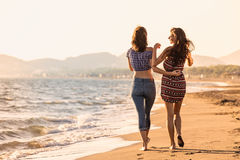 俏丽的女孩获得与她的女朋友的一个乐趣海滩的 库存图片