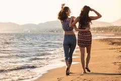 俏丽的女孩获得与她的女朋友的一个乐趣海滩的 库存照片