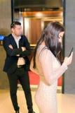 俏丽的女孩藏品智能手机在她的手和采取图片上在旅馆 免版税图库摄影