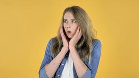 俏丽的女孩被迷惑和被惊吓在黄色背景的问题 股票视频