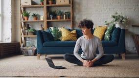 俏丽的女孩观看关于瑜伽的网上教训在膝上型计算机并且实践在家单独坐地板做 股票录像