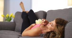 俏丽的女孩观看的电影和吃玉米花 免版税库存图片