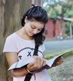俏丽的女孩读取在结构树下。 图库摄影