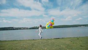 俏丽的女孩跑到与五颜六色的气球的河海湾 股票录像