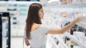俏丽的女孩选择在化妆用品的香水购物,喷洒了它在测试器,慢动作 股票视频