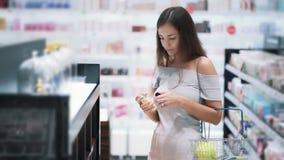 俏丽的女孩选择在化妆用品的香水购物,嗅它,慢动作 影视素材