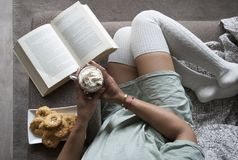 俏丽的女孩阅读书在家在长沙发用热巧克力牛奶和曲奇饼 免版税库存照片
