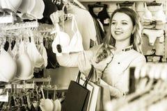 俏丽的女孩顾客审查的胸罩在商店 免版税图库摄影
