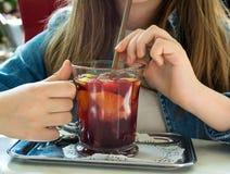 俏丽的女孩饮用的茶用新鲜水果 库存图片