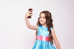 俏丽的女孩 在电话的照片 豪华的蓝色礼服 免版税库存图片