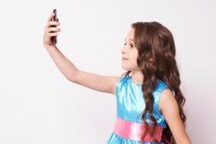 俏丽的女孩 在电话的照片 豪华的蓝色礼服 免版税图库摄影