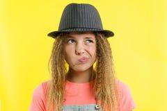 俏丽的女孩12-13岁白肤金发与在帽子的卷发,在旁边沉思神色,考虑学校 免版税库存照片