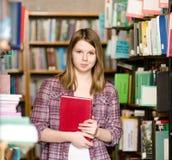 俏丽的女孩画象在看照相机的图书馆里 免版税图库摄影