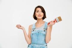 年轻俏丽的女孩画象,看惊奇,举行paintin 免版税库存照片