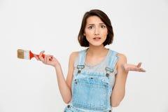 年轻俏丽的女孩画象,看惊奇,举行paintin 免版税库存图片