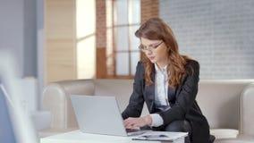 俏丽的女实业家研究膝上型计算机的在昂贵的办公室,负责任的官员 图库摄影