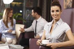 俏丽的女实业家饮用的咖啡画象  图库摄影