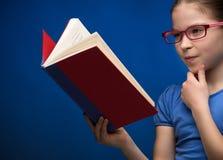 俏丽的女小学生阅读书。 免版税图库摄影