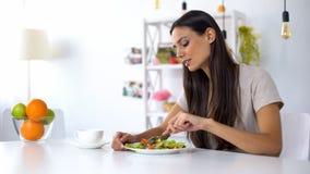 俏丽的女性吃沙拉,减肥的,营养健康素食 免版税库存图片