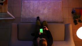 俏丽的女性少年看着电视特写镜头顶面射击使用在网上购物的电话的,当坐长沙发时 股票视频