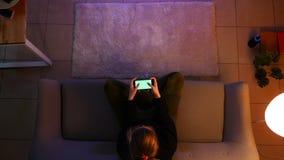 俏丽的女性少年看着电视特写镜头顶面射击使用打电子游戏的电话的,当坐长沙发时 股票视频