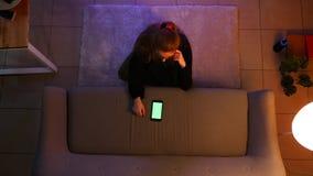 俏丽的女性少年看着电视特写镜头顶面射击使用电话的有绿色屏幕的,当坐地毯时 股票视频