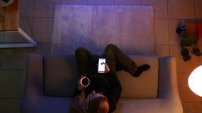 俏丽的女性少年看着电视特写镜头顶面射击使用遥控的在电话,当坐长沙发时 影视素材