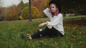 俏丽的女性行家基于公园的草坪和姿势在照相机 影视素材