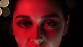 俏丽的女性面孔特写镜头射击与诱人的构成的与红色霓虹灯和摆在前面的bokeh背景 股票录像